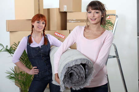 two girlfriends moving in their new apartment Stock Photo - 13974434
