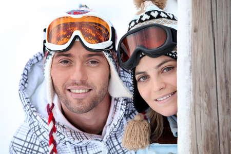 Playful young couple enjoying their skiing holiday photo