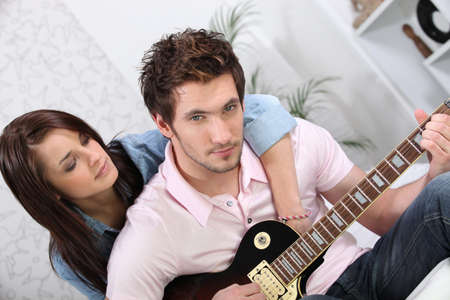 Woman hugging her boyfriend while he plays the guitar photo