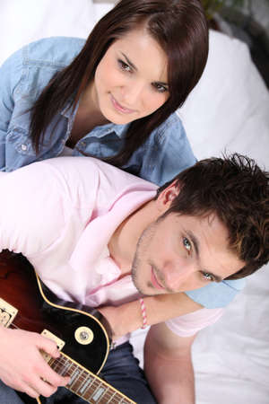 a young couple on bed, the man is playing guitar photo