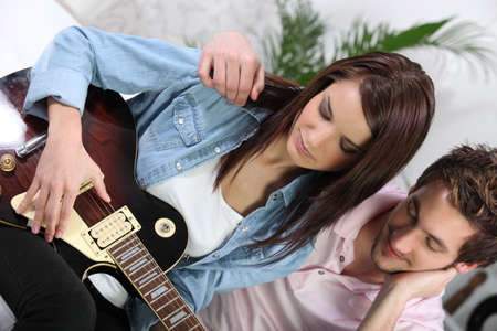 a woman playing guitar and her boyfriend photo