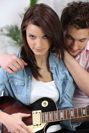 electric guitar: Couple sat with electric guitar