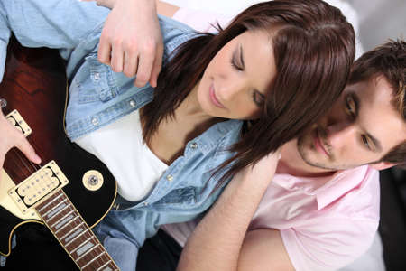 enraptured: Man looking girl playing guitar Stock Photo