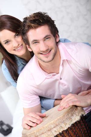 all smiles: young couple all smiles with djembe drum
