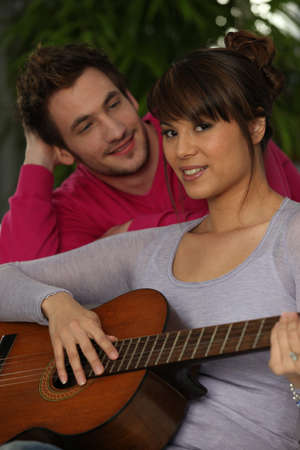 Smiling boy and girl playing guitar photo