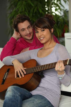 Young couple playing a guitar at home photo