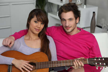 Woman playing the guitar for her boyfriend photo