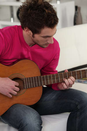 man playing guitar at home photo