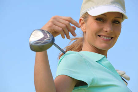 Woman with golf club and visor photo