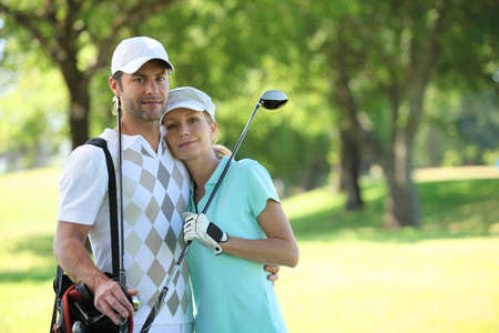 Golfing couple hugging on a course photo