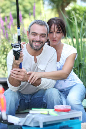 hair back: Couple with fishing rod Stock Photo