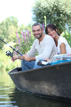Couple fishing in a boat on a lake photo