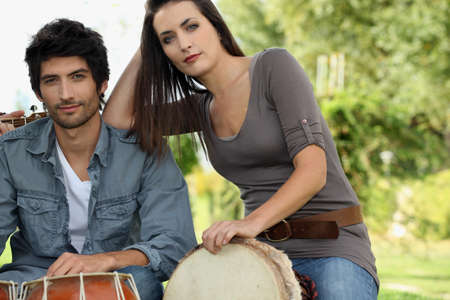Couple playing bongo drums outdoors photo