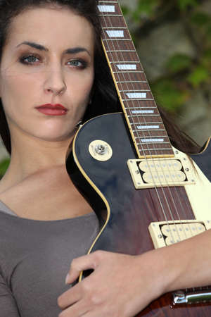 young woman playing guitar photo
