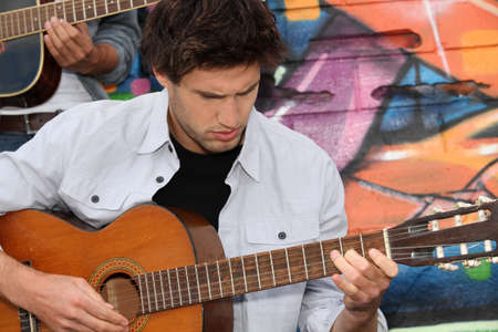 Musician with guitar in front of painted wall Stock Photo - 13944657