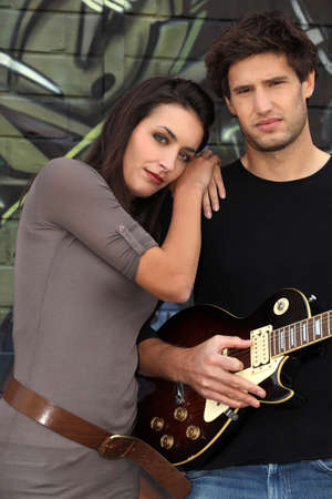 Couple with guitar in front of painted wall Stock Photo - 13945896