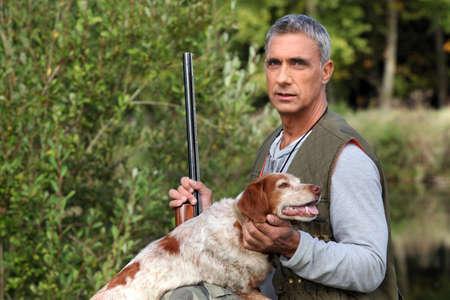 perro de caza: cazador de tomar un fusil y acariciar a un perro de caza