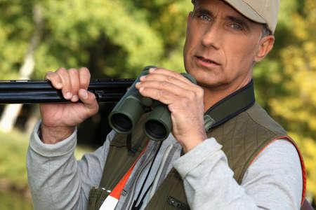 cull: Hunter with shotgun and binoculars Stock Photo
