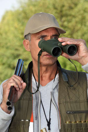 deer hunter: Hunter looking through binoculars Stock Photo