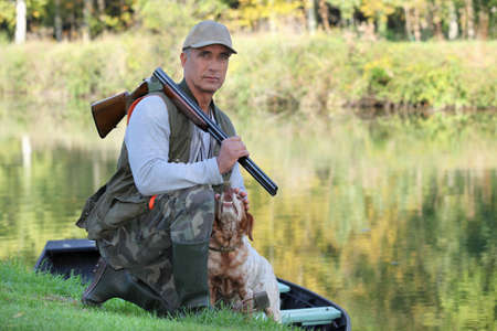 hunting rifle: Hunter with dog crouched Stock Photo