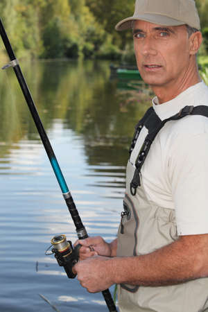impermeable: 50 years old man fishing on the edge of a river Stock Photo