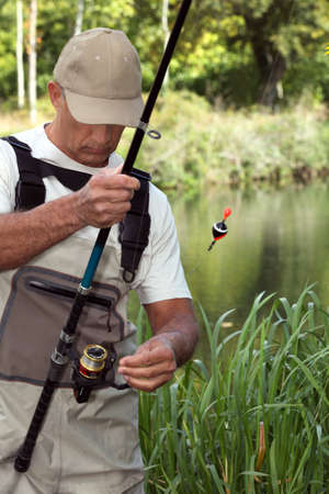 backwoods: man watching his fishing rod in front of a river Stock Photo