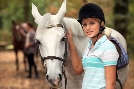 Girl stroking white horse photo