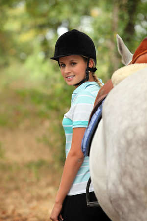 equitation: Woman standing next to her horse