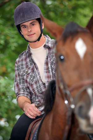 young man riding a horse photo
