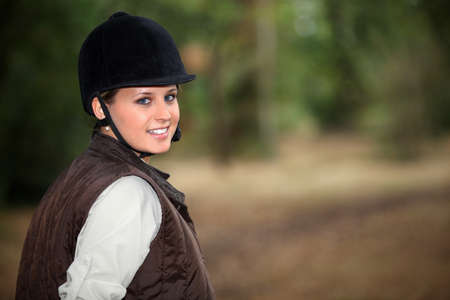 Young female horseback rider on a forest trail photo