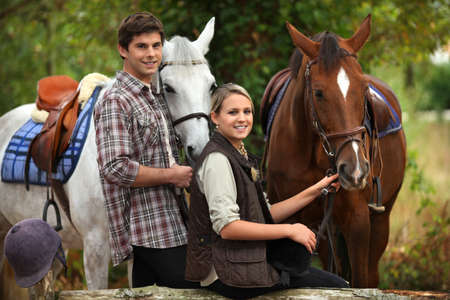 horses in field: Young people horseriding