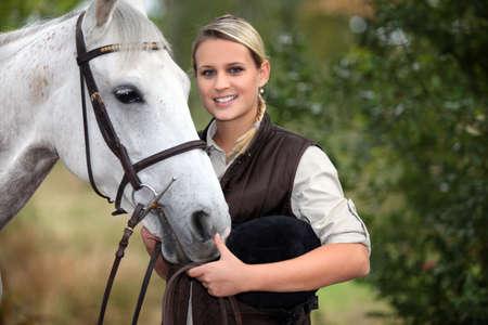 femme et cheval: jeune femme qui prend soin de son cheval
