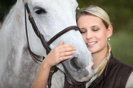 mujer en caballo: Mujer rubia acariciando a caballo