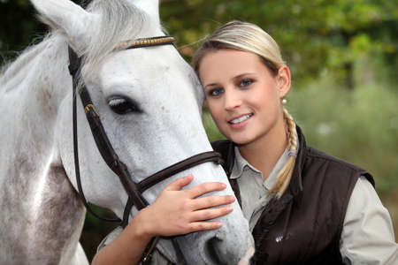 holidays vacancy: Blond woman with her horse Stock Photo