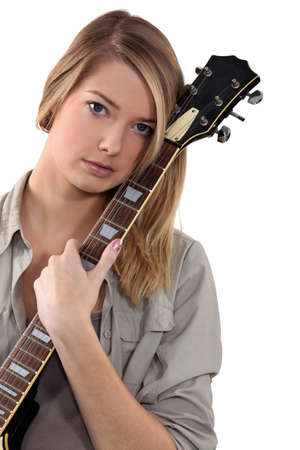 Blond teenage girl posing with guitar photo