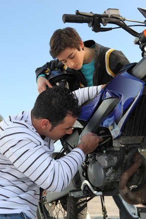 Father and son repairing their motorcycle