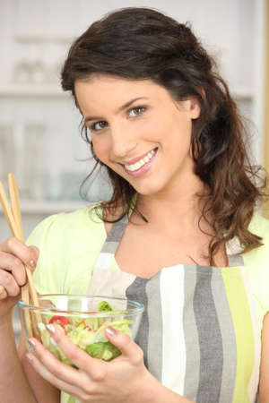 Woman mixing bowl of salad leaves photo