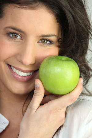 naturally: Young woman holding green apple