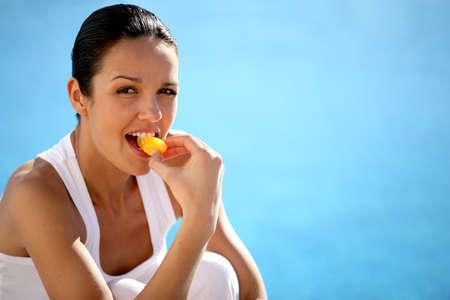 Woman kneeling by swimming pool eating fruit photo