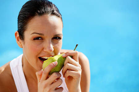 facing to camera: Woman eating a pear Stock Photo
