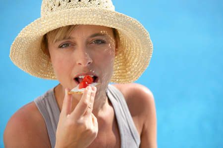 straw hat: Woman in straw hat eating strawberry