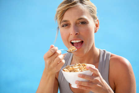 Healthy woman eating bowl of cereals photo