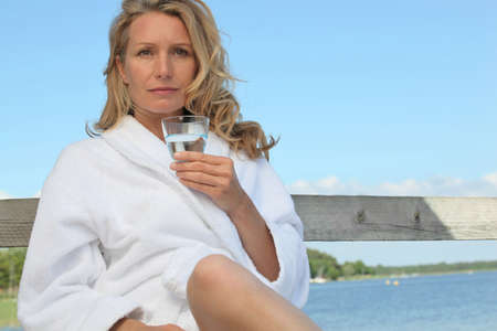 Woman sat by lake in bath robe photo