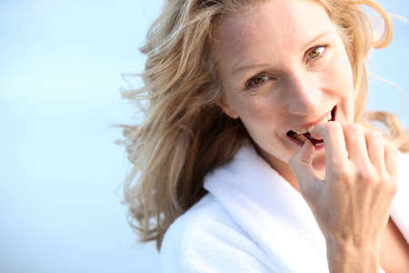 robes: Woman eating chocolate Stock Photo