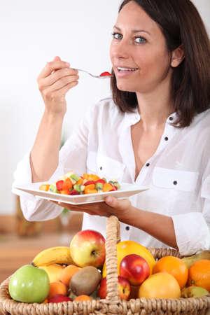 conscious: Health conscious brunette eating fruit salad