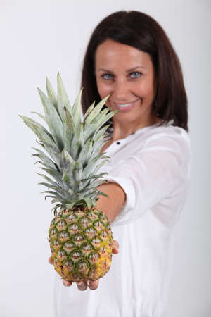 spikey: Woman holding a pineapple Stock Photo