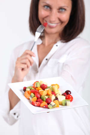 Woman eating fruit salad photo