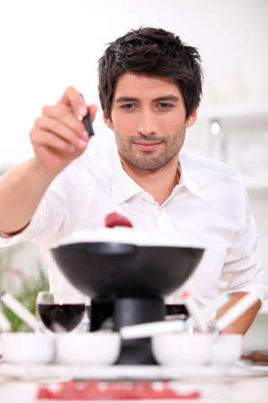 Man dipping raw beef into fondue Stock Photo - 13951280