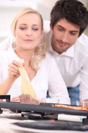 Couple cooking surf and turf on a tabletop hotplate photo