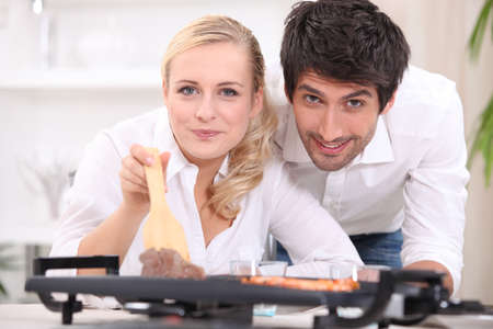 Couple cooking steak and prawns on a table top hotplate photo